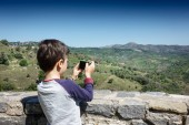 Rear view of boy photographing landscape at Crete, Greece