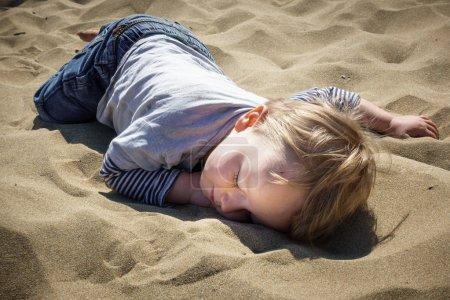 Photo pour Gros plan d'un garçon vêtu de façon décontractée dormant sur le sable - image libre de droit