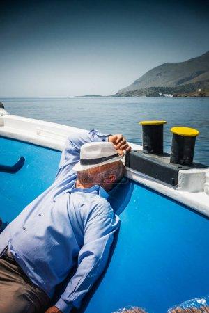 Photo pour Homme au visage couvert de chapeau dormant sur le pont du bateau - image libre de droit