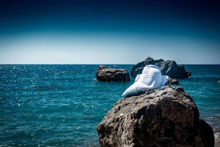 Photo pour Vue arrière du garçon enveloppé dans une serviette tout en étant assis sur un rocher surplombant l'eau bleue ondulée - image libre de droit