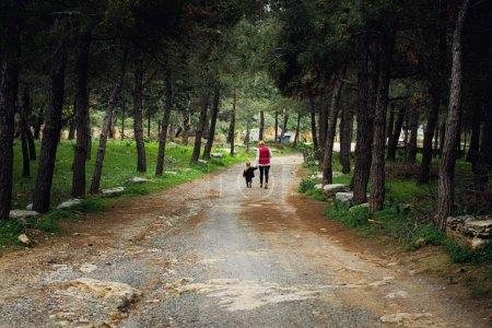 Photo pour Vue arrière d'une femme avec un enfant marchant sur un sentier près d'un arbre - image libre de droit