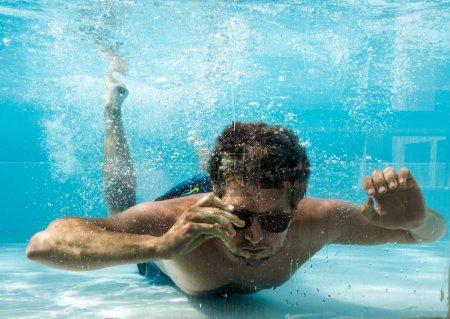 Photo pour Portrait d'homme en lunettes de soleil nageant sous l'eau dans la piscine, Crète, Grèce - image libre de droit