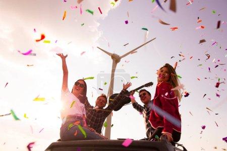 Photo pour Joyeuses jeunes amis profitant de la fête en plein air avec confettis dans la nature - image libre de droit