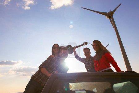 Photo pour Portrait groupe d'adolescents amis étudiants hipster pendant la fête et profiter de la guitare en plein air. Ils sourient et regardent la caméra posant sur le toit ouvrant de la voiture dans la zone naturelle du parc éolien le jour ensoleillé d'été tandis que la route insouciante voyage - image libre de droit