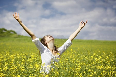 Foto de Mujer joven de pie en el campo de colza amarilla levantando los brazos expresando gratitud o libertad . - Imagen libre de derechos