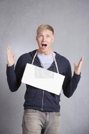 Photo pour Nouvelles choquantes : Surpris malheureux homme présentant panneau blanc vierge avec espace pour le texte isolé sur fond gris . - image libre de droit