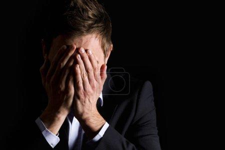 Photo pour Portrait discret d'un chef de bureau désespéré en costume sombre couvrant son visage des deux mains, isolé sur fond noir avec espace de copie . - image libre de droit