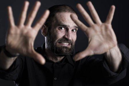 Photo pour Homme effrayé regardant effrayé, indiquant STOP avec les deux mains, isolé sur fond noir . - image libre de droit