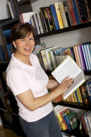 Photo for Smiling senior woman standing in front of bookshelf at home and carrying books. - Royalty Free Image