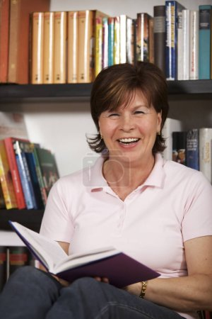 Photo for Laughing senior woman sitting on floor in front of bookshelf at home and reading a book. - Royalty Free Image
