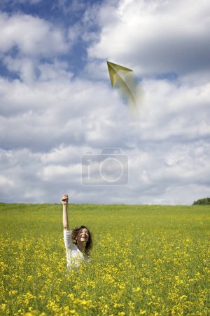 Photo for Smiling woman in yellow rapeseed field throwing  a paper plane. - Royalty Free Image