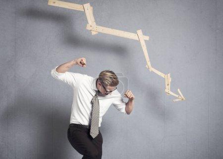 Photo pour Concept : Accident d'entreprise. Jeune homme d'affaires courroucé devant un graphique d'affaires à tendance négative, isolé sur fond gris . - image libre de droit