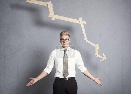 Photo pour Concept : déclin des affaires. Jeune homme d'affaires mécontent devant le graphique d'affaires pointant vers le bas, isolé sur fond gris . - image libre de droit