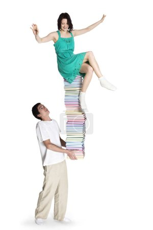 Photo for Young man carrying a high stack of colorful books with girl sitting on top of it trying to balance, isolated on white background. - Royalty Free Image