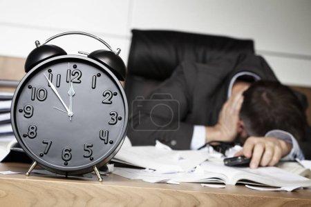 Photo pour Senior homme d'affaires étant choqué après avoir reçu de mauvaises nouvelles sur le téléphone portable, assis au bureau derrière le réveil montrant cinq minutes à douze . - image libre de droit