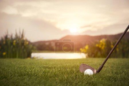 Photo pour Gros plan du club de golf avec balle au coucher du soleil, avec fairway en arrière-plan . - image libre de droit
