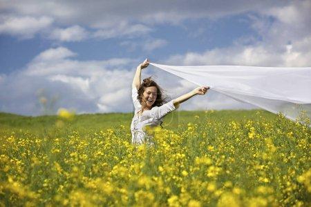 Photo pour Jeune femme heureuse debout dans un champ de colza jaune tenant un long morceau de tissu blanc dans le vent . - image libre de droit