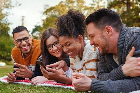 Photo pour Sourire groupe diversifié d'amis regardant le téléphone mobile à l'extérieur dans le parc - image libre de droit