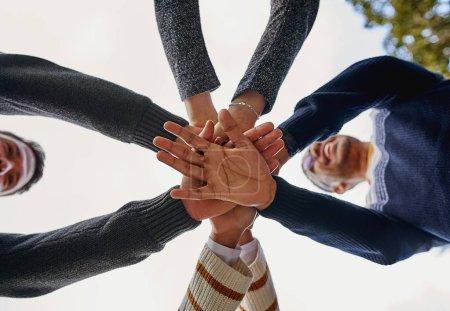 Photo pour Directement en dessous du plan d'amis multiethniques empilant les mains - image libre de droit