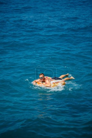 Photo for A young man floats on an inflatable air ring circle in the sea with blue water. Festive holiday on a happy sunny day. - Royalty Free Image