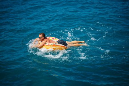 Photo for A man lies on a large inflatable rubber circle and floats on the blue sea on a bright sunny summer day - Royalty Free Image