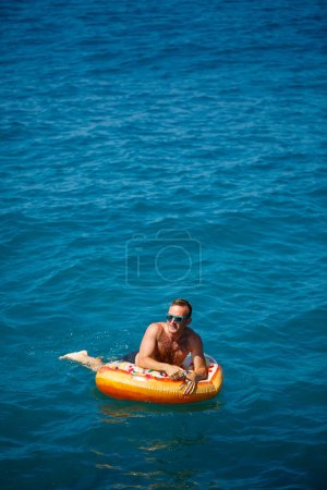 Photo for Young man on an inflatable ring in the sea resting and swimming on a sunny day - Royalty Free Image
