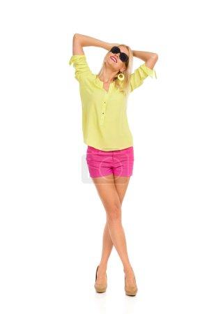 Photo pour Détendu de belle femme blonde en short rose, une chemise jaune et des talons hauts est debout avec les mains derrière la tête et regardant vers le haut. Studio de pleine longueur coup isolé sur blanc. - image libre de droit