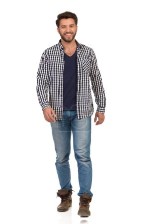 Photo for Smiling man in boots, jeans and unbuttoned, lumberjack shirt is walking towards camera. Full length studio shot isolated on white. - Royalty Free Image