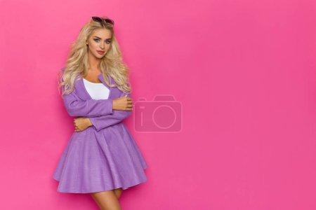 Photo pour Belle femme blonde en mini jupe violette et veste déboutonné pose avec des bras croisés et regardant la caméra. Trois quarts de longueur de Studio tourné sur le fond rose. - image libre de droit