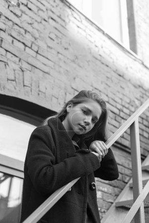 Photo pour Jeune fille mélancolique en manteau noir debout sur les escaliers avec mur de briques vintage sur un fond. Concept de solitude. Image en noir et blanc - image libre de droit