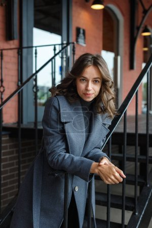 Photo for Young thoughtful pretty girl in gray coat and turtleneck poses in front of red building. Street style portrait photo session of attractive female, urban photoshoot of beautiful elegant model - Royalty Free Image