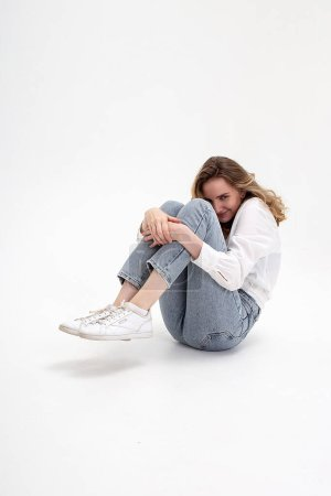 young cute smiling caucasian girl posing in white shirt, blue jeans at studio