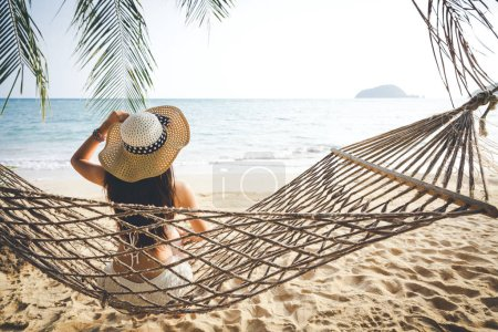 Photo for Summer vacations concept, Happy woman with white bikini, hat and shorts Jeans relaxing in hammock on tropical beach at sunset, Koh mak, Thailand - Royalty Free Image