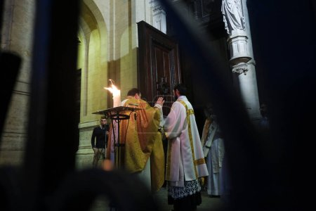 Photo for People take part in Easter vigil mass behind closed doors in Catholic church of Sainte-Catherine in Brussels, Belgium, on Holy and Great Saturday, April 11, 2020. - Royalty Free Image