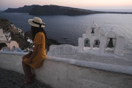 Photo pour People look at the sunset in the town of Oia in the island of Santorini, Greece on Aug. 13, 2020. - image libre de droit