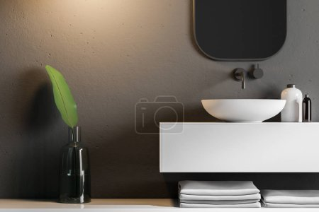 Bathroom interior with black walls, a sink standing on a white countertop and a vertical mirror hanging above it. A close up. 3d rendering