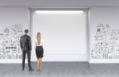 Rear view of young and successful business partners wearing suits looking at a blank horizontal mock up advertisement poster in gallery with business and start up graffiti like sketches on white walls