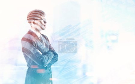 Side view of a young handsome businessman wearing glasses and a gray suit and standing with crossed arms against a cityscape. Leadership concept. Toned image double exposure mock up.