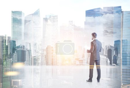 Young businessman with a beard wearing a gray suit is standing and holding papers. He is looking forward. A modern cityscape. Toned image mock up