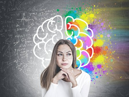 Head and shoulders portrait of a beautiful young woman with fair hair wearing white and thinking looking sideways. A blackboard with a colorful brain sketch