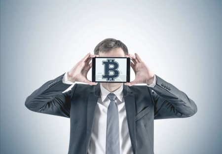 Cropped portrait of an unrecognizable young caucasian businessman with fair hair holding a tablet computer with a bitcoin symbol in front of his face. Gray background