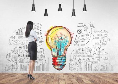 Photo pour Portrait complet d'une jeune femme d'affaires caucasienne méconnaissable portant une jupe et une chemise à talons hauts regardant un mur avec une ampoule colorée et des icônes d'affaires - image libre de droit