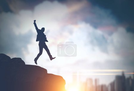 Silhouette of a young businessman jumping on a rock against a big city sky background. Concept of business success. Toned image mock up