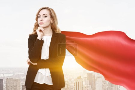 Confident and successful businesswoman wearing a suit and a red cape standing against a morning cityscape. Young, attractive and daring. 3d rendering mock up toned image
