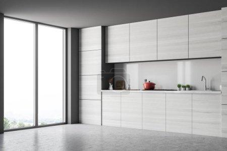 graue Küchenecke mit Arbeitsplatten und Dachbodenfenstern. Betonboden und graue Wände. 3D-Rendering-Attrappe