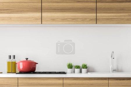 Küchenarbeitsplatten aus Holz mit eingebautem Herd, einem Topf darauf und kleinen Pflanzen. Olivenöl. Konzept des Kochens zu Hause und familiäre Werte. 3D-Rendering-Attrappe