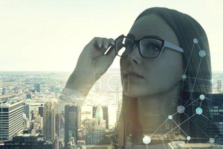 Nachdenkliche junge Geschäftsfrau mit Brille, die sich auf ein morgendliches Stadtbild mit einem Netzwerk-Hologramm in der Ecke freut. getöntes Bild Doppelbelichtung Attrappe