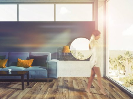 Woman walking in a blue living room interior with a wooden floor, a blue sofa and a round mirror on the closet. 3d rendering toned image