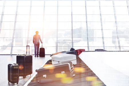 Gray, white and pink suitcases on airport conveyor belt in a room with panoramic windows. Businessman. 3d rendering mock up toned image double exposure