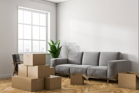 Empty white room corner with white walls, a wooden floor, a large window and stacks of closed cardboard boxes. A gray sofa. Concept of moving in. 3d rendering mock up